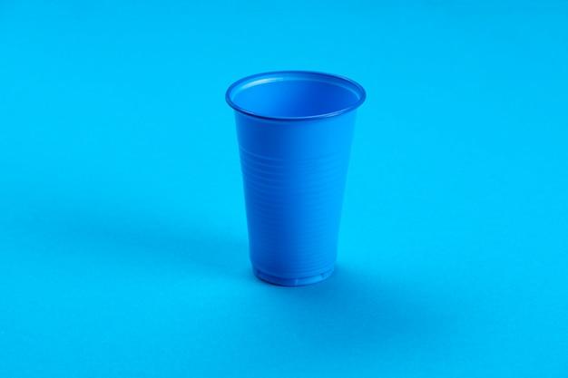 青い空のプラスチックカップ。プラスチックのリサイクル。プラスチック廃棄物。