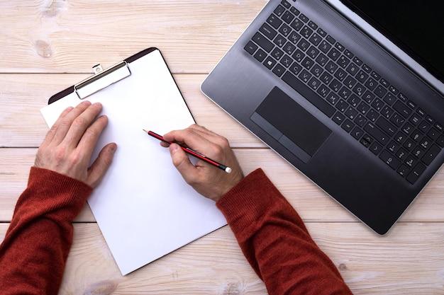 男はラップトップで働いて、手は木製のテーブル、トップビューで鉛筆でクリップボードに書き込む