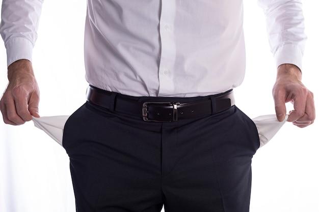 空のポケットを持ったビジネスマン、男の手はズボンの空のポケットを保持しています。