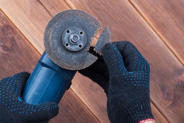 Точильщик со сломанным лезвием на деревянном столе. опасность использования электроинструмента