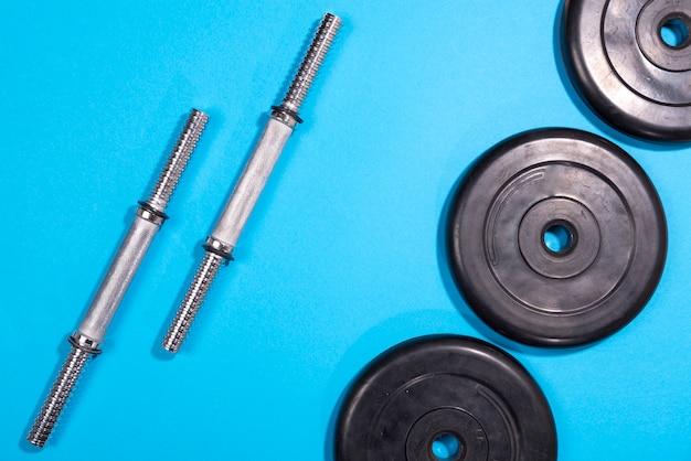 Фитнес или бодибилдинг. спортивное оборудование, штанга, гантели, вид сверху