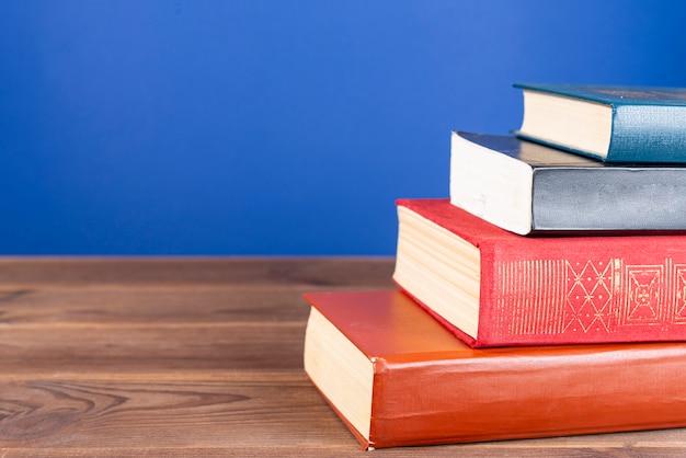 多くのハードカバーの本、木製のテーブルにマルチカラーの本のシンプルな構成