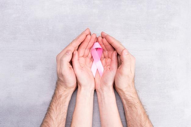 Концепция здравоохранения и медицины - женские и мужские руки держат розовую ленту осведомленности рака молочной железы