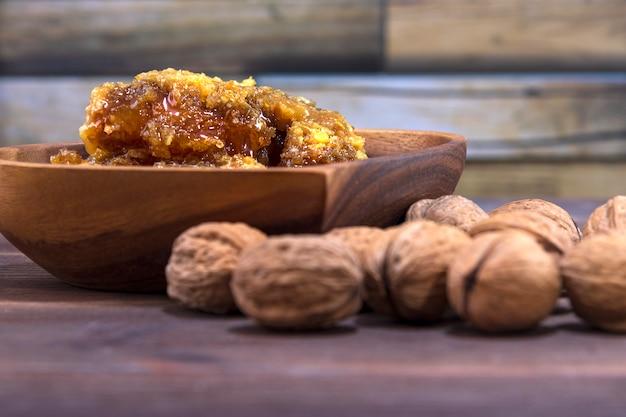 Соты с медом в деревянной тарелке и много грецких орехов в скорлупе на деревянной поверхности