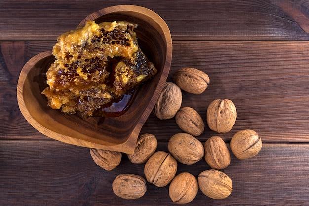 Соты с медом в деревянной тарелке и много грецких орехов в скорлупе на деревянной поверхности. вид сверху