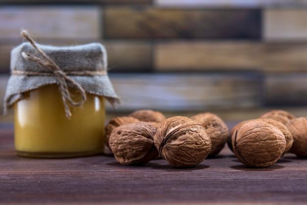 Мед в стеклянной банке и много грецких орехов в скорлупе на деревянной поверхности