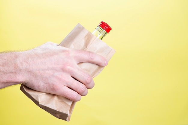 Мужская рука с бутылкой алкоголя в бумажном пакете на желтом