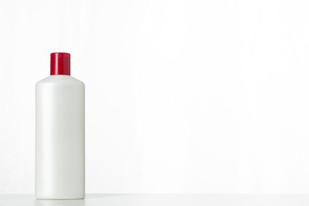 Безымянная пластиковая бутылка из-под косметического продукта с красной крышкой на белом фоне