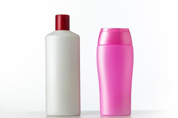 Две безымянные пластиковые бутылки белого и розового цвета из-под косметического продукта на белом фоне
