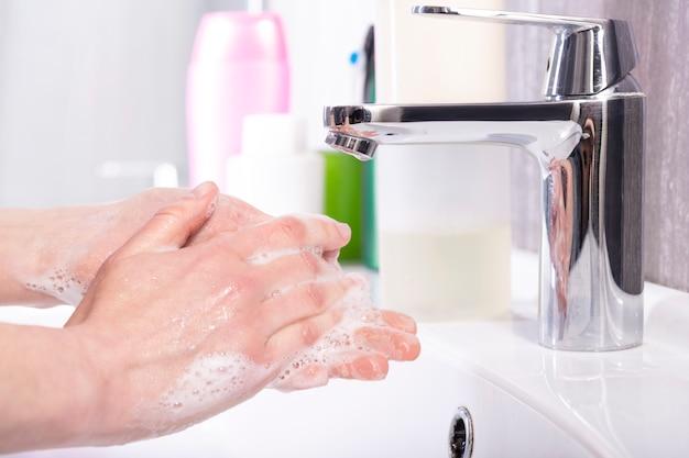 モダンなバスルームの蛇口の下で石鹸で手を洗う女性