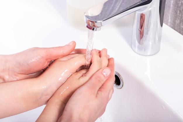 ママはモダンなバスルームの蛇口の下で赤ちゃんの手を洗う