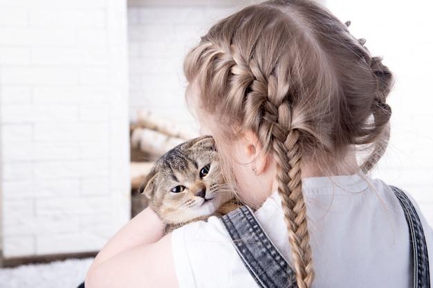 Красивая маленькая девочка обнимает британского котенка породы фолд