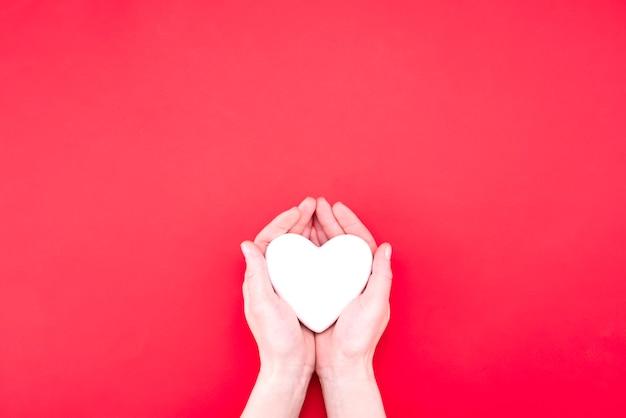 Женщина держит декоративное сердце на красном