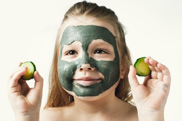 バスタオルで粘土化粧品マスクを持つ面白い少女