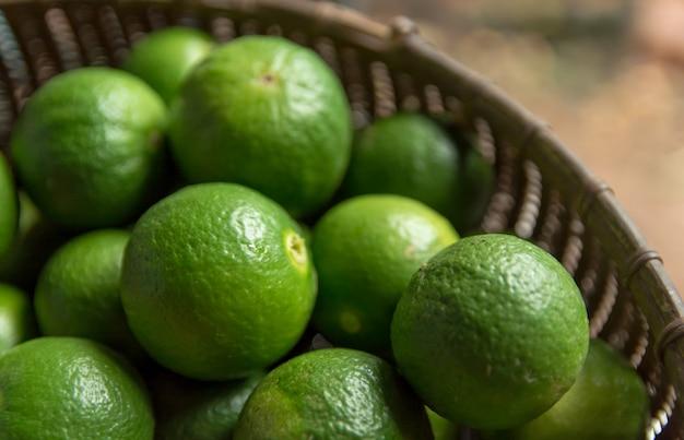 ライムの柑橘系の果物、竹のバスケットの背景
