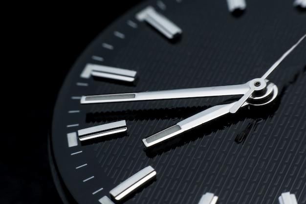 黒い時計の文字盤の背景に時計回りにクローズアップ。レトロなスタイルの腕時計