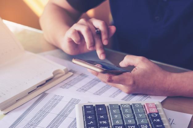 電卓を使用して、オフィスの机の上にスマートフォンを使用して女性の手を閉じる。