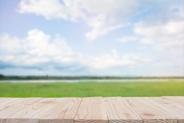 空の木の板テーブルの上にぼやけている青い空と川の背景。コピースペース