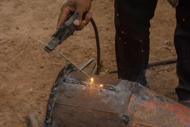 溶接機は工事現場で金属配管を溶接しています