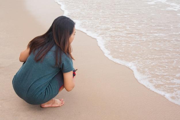 木の枝と砂浜で書く女