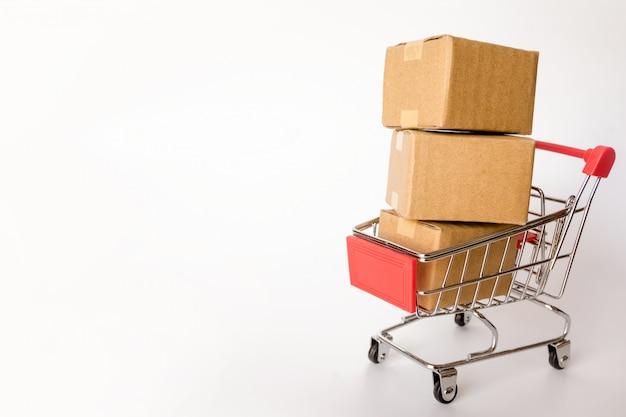 カートンや白地に赤のショッピングカートの中の紙箱。コピースペースあり