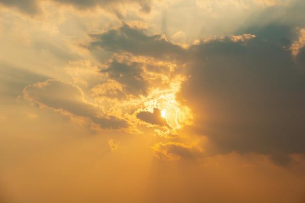 Солнечный свет захода солнца через предпосылку облаков.