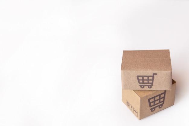 段ボール箱や白い背景の上のスーパーマーケットのロゴ入り小包。コピースペースあり