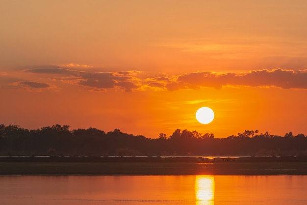 湖の夕日。湖の風景以上の背景の上の雲の後ろに美しい夕日。夕焼け雲と劇的な空