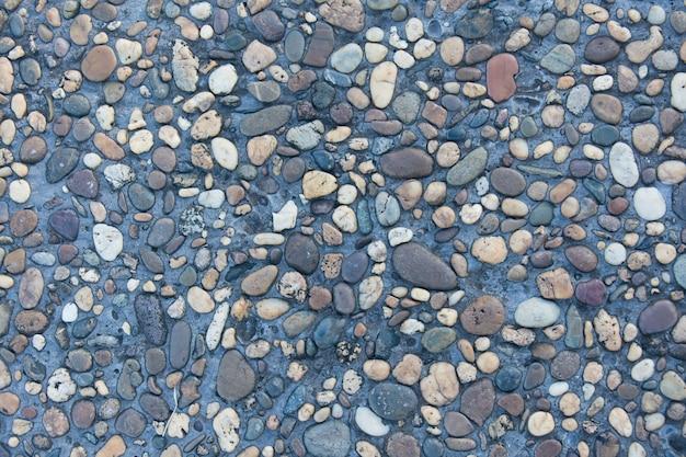 シームレスな砂と小さな砂利石のテクスチャ背景