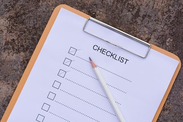 チェックリストのコンセプト - チェックリスト、紙と木製のテーブルの上のチェックリストの単語を持つペン