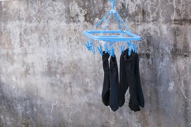 衣服止め釘や洗濯はさみがひもに掛かっています。プラスチック製衣服止め釘
