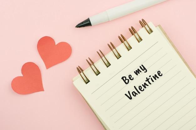 ピンクの背景に空白のペンを置くと黄色のノートブック。
