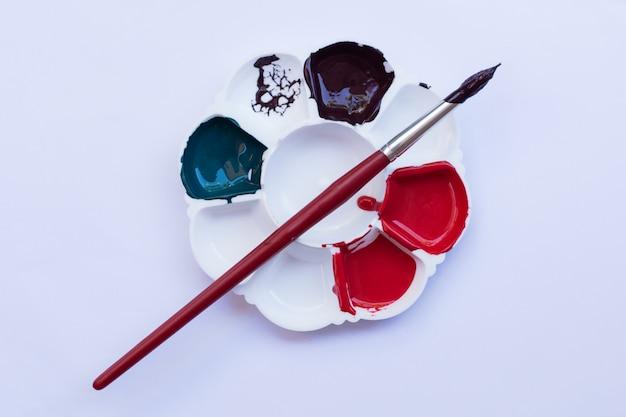 白い背景の上の様々な色の塗料でアーティストパレット