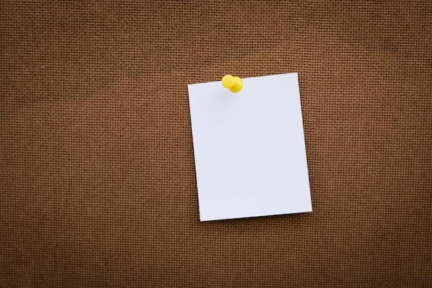 空白のホワイトペーパーメモを白い画鋲でコルク板に固定、利用可能なコピースペース