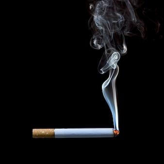 黒の背景にタバコを吸う