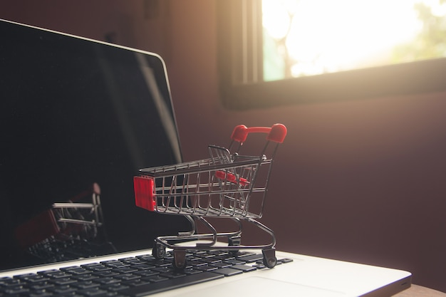 Ходя по магазинам онлайн концепция - магазинная тележкаа или вагонетка на клавиатуре компьтер-книжки. сервис покупок в интернете.