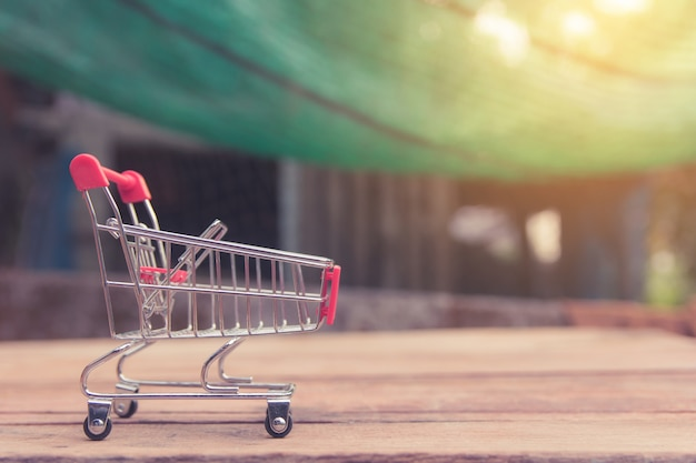 Концепция покупок - опорожните красную магазинную тележкау на коричневой деревянной таблице. покупатели в интернете могут делать покупки из дома и с доставкой.
