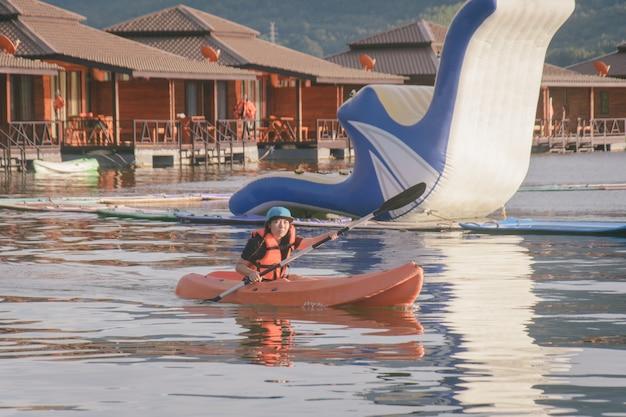 オレンジ色のライフジャケット、湖でのカヤックの若い女性。ウォーターパークでカヌーをする幸せな若い女