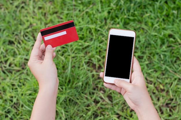 女性両手クレジットカードとセル、オンラインショッピングのためのスマートフォンを使用して