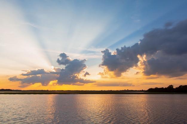 夕日の反射ラグーン。雲とオーバーラグーンの風景の上の青い空の後ろに美しい夕日