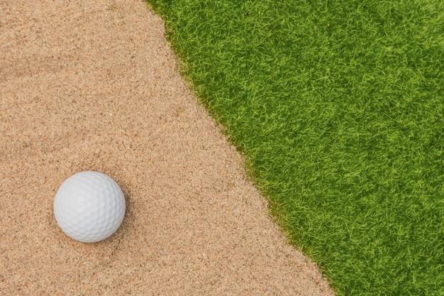 ゴルフ場の砂のバンカーで白いゴルフボール