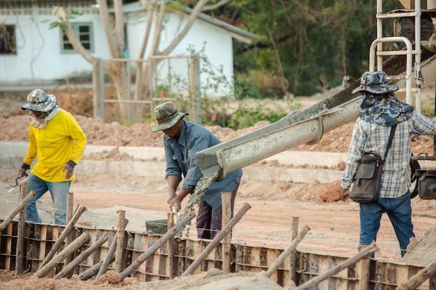 Автобетоносмеситель. рабочие заливают бетон на стройплощадку