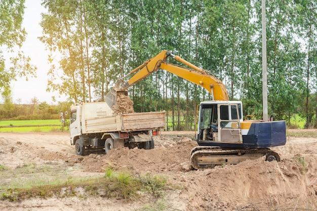 建設現場でダンプトラックに土をロードする黄色の掘削機機械