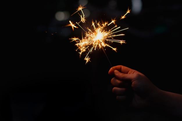 燃える線香花火を持つ女性の手