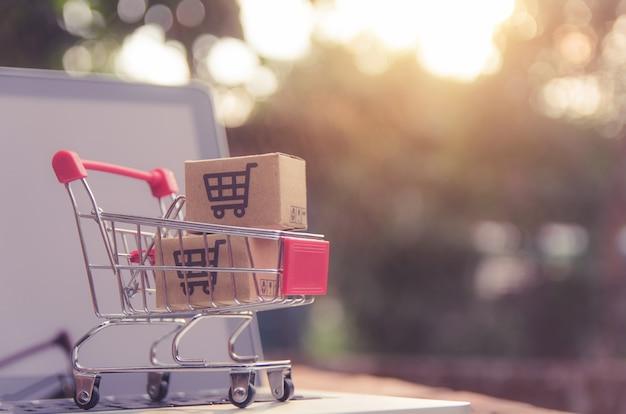 ノートパソコンのキーボードのトロリーにショッピングカートのロゴが入った小包または紙の箱。