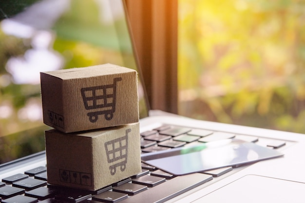 ショッピングカートのロゴとラップトップキーボードのクレジットカードが入った紙パックまたは小包。