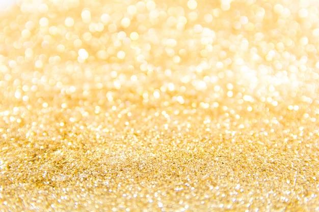 ゴールドラメの背景をデフォーカス。ゴールドの抽象的なボケ背景。クリスマスの抽象的な背景