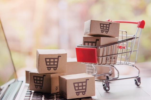 Покупки онлайн концепции - посылки или бумажные коробки с логотипом корзина в тележке на клавиатуре ноутбука. сервис покупок в интернете. предлагает доставку на дом.