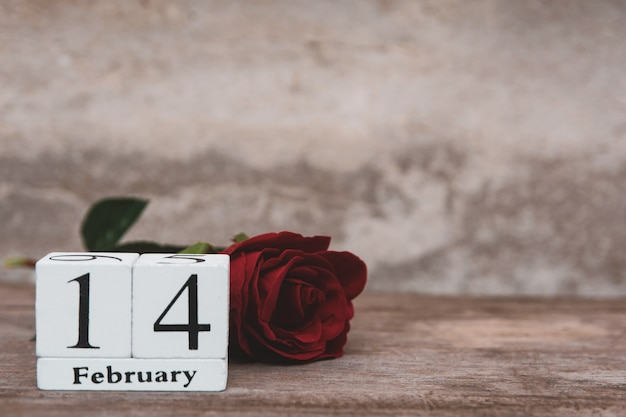 木製の白いブロックカレンダーと赤いバラ