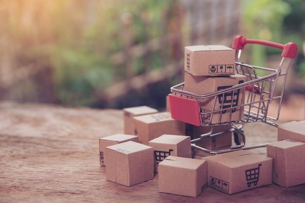 Концепция покупок - коробки или бумажные коробки в магазинной тележкае на коричневой деревянной таблице. покупатели в интернете могут делать покупки из дома и с доставкой. с копией пространства